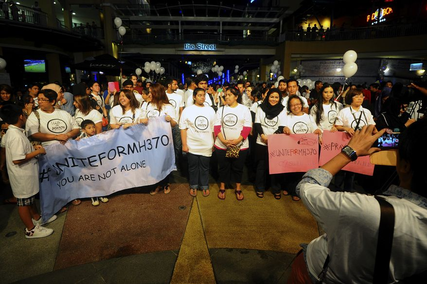 In this picture taken on Tuesday, March 18, 2014, a journalist takes a picture of the crowd during an interfaith event for the missing Malaysia Airlines, flight MH370 at a shopping mall in Petaling Jaya outside Kuala Lumpur, Malaysia. The Malaysia Airline plane, which was heading to Beijing, disappeared early March 8 about an hour after take-off from Kuala Lumpur. Military radar showed the plane backtracked toward the Strait of Malacca, just west of Malaysia. Aircraft and ships are scouring two giant arcs of territory amounting to the size of Australia - half of it in the remote waters of the southern Indian Ocean. (AP Photo/Joshua Paul)