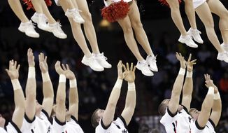Cincinnati cheerleaders reach to catch other cheerleaders after tossing them into the air during a timeout in the second half during the second round of the NCAA men's college basketball tournament in Spokane, Wash., Thursday, March 20, 2014. Harvard won 61-57. (AP Photo/Elaine Thompson)