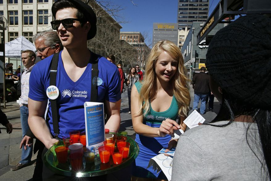 Meghan McMahon and fellow model Alex Terranova hand out stickers and juice on an outdoor pedestrian mall, encouraging the public to get health coverage under the Affordable Care Act, during a promotional campaign launched by Colorado HealthOP, a independent non-profit health care co-op, in Denver, Thursday March 20, 2014. More than 250,000 Coloradans have become covered through the state-run insurance exchange since enrollment began October 1, 2013, and those who still do not have health insurance have two more weeks to get coverage or pay a fine. (AP Photo/Brennan Linsley)