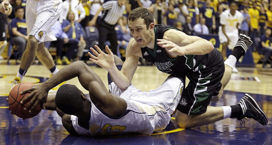 California's Jabari Bird attempts to pass from the floor away from Utah Valley's Mitch Bruneel in the first half of an NCAA college basketball game Wednesday, March 19, 2014, in Berkeley, Calif. (AP Photo/Ben Margot)