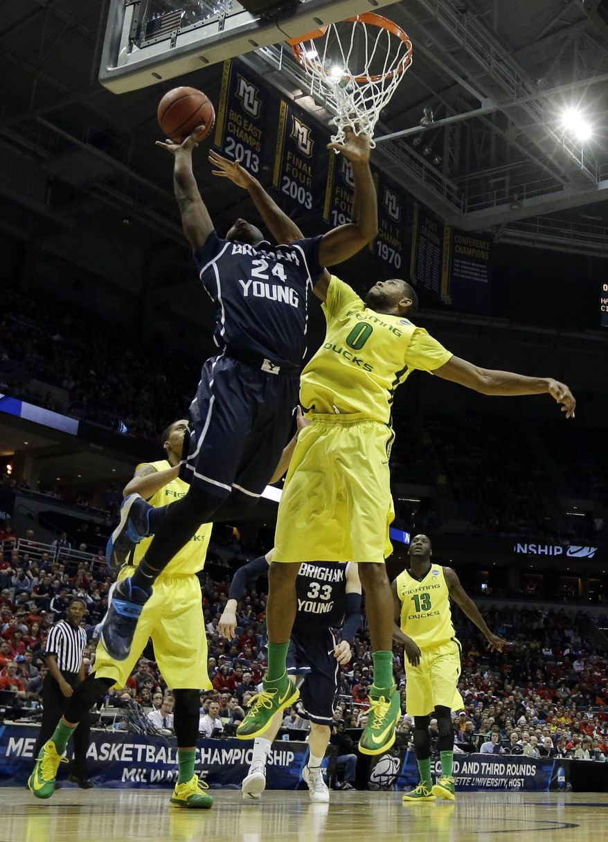 BYU guard Frank Bartley IV (24) goes up for a shot against Oregon forward Mike Moser (0) during the first half of a second-round game in the NCAA college basketball tournament Thursday, March 20, 2014, in Milwaukee. (AP Photo/Morry Gash)
