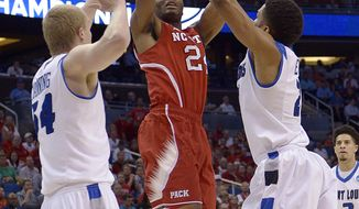 North Carolina State forward T.J. Warren (24) shoots as Saint Louis center John Manning, left and forward Dwayne Evans (21) defend during the first half in a second-round game in the NCAA college basketball tournament Thursday, March 20, 2014, in Orlando, Fla. (AP Photo/Phelan Ebenhack)