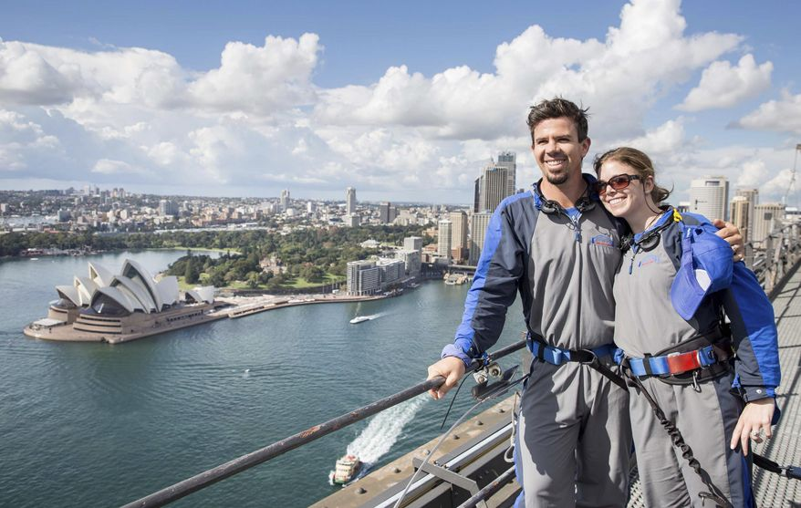 In this photo released by Destination NSW, Arizona Diamondbacks infielder Cliff Pennington poses with his wife after climbing the Sydney Harbour Bridge in Sydney Thursday, March 20, 2014. The Diamondbacks will play the Los Angeles Dodgers in their Major League Baseball season opening games at the Sydney Cricket Ground on Saturday and Sunday. (AP Photo/Destination NSW, James Horan)