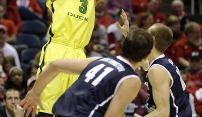 Oregon guard Joseph Young (3) takes a shot over BYU's Luke Worthington (41) and Josh Sharp during the first half of a second-round game in the NCAA college basketball tournament Thursday, March 20, 2014, in Milwaukee. (AP Photo/Jeffrey Phelps)