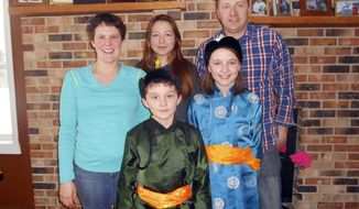 ADVANCE FOR SUNDAY, MARCH 23- In a March 2014 photo front row, left to right, host brother Jared Reynolds and host sister Molly Reynolds, both dressed in traditional Mongolian attire are photographed with their mother Heidi Reynolds, exchange student Oyundari Uurdsaikhan, who goes by the name Daria, and father Mick Reynolds  in Hardwood, Mich. Mick and Heidi have been traveling to Mongolia for the past 14 years in order to teach English in rural areas. This year, instead of going there themselves, a little bit of Mongolia came to them. Daria, has been living with the Reynolds family and attending North Dickinson High School for the 2013-2014 academic year. (AP Photo/The Daily News, Nikki Younk)