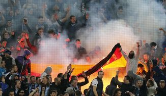 Zenit supporters burn a German flag during the Champions League round of 16 second leg soccer match between Borussia Dortmund and FC Zenit in Dortmund, Germany, Wednesday, March19,2014. (AP Photo/Frank Augstein)
