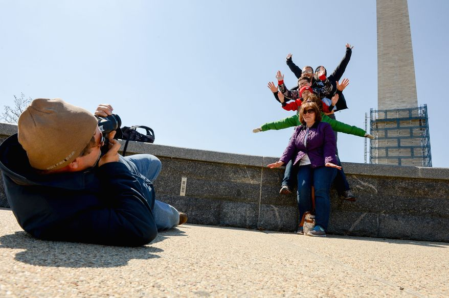 The Lund family from Wisconsin poses together Thursday in front of the Washington Monument, which is set to reopen in May, officials have announced. (photographs by andrew harnik/the washington times)