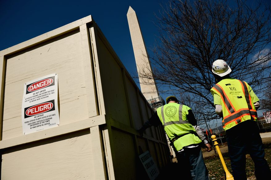 Construction workers take a break near the Washington Monument on Thursday. Construction on the landmark began in late 2012 after an earthquake sent a jolt down the East Coast in August 2011.