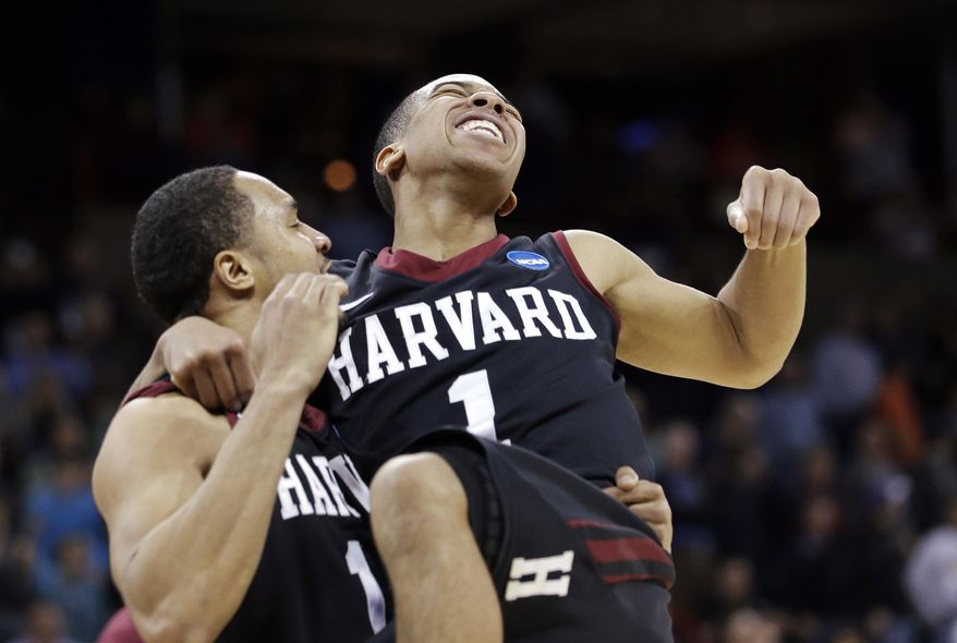 Harvard's Siyani Chambers, right, leaps into the arms of teammate Brandyn Curry after the team beat Cincinnati in the second round of the NCAA college basketball tournament in Spokane, Wash., Thursday, March 20, 2014. Harvard won 61-57. (AP Photo/Elaine Thompson)