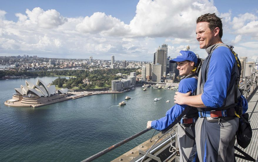 In this photo released by Destination NSW, Arizona Diamondbacks' pitcher Will Harris with his wife enjoys viewing from the Sydney Harbour Bridge in Sydney, Thursday, March 20, 2014. The Diamondbacks will play the Los Angeles Dodgers in their Major League Baseball season opening games at the Sydney Cricket Ground on Saturday and Sunday. (AP Photo/Destination NSW, James Horan)
