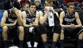 BYU's Josh Sharp, left, Matt Carlino, Eric Mika, and Skyler Halford watch from the bench during the second half of a second-round game in the NCAA college basketball tournament Thursday, March 20, 2014, in Milwaukee. Oregon won 87-68. (AP Photo/Jeffrey Phelps)