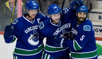 Vancouver Canucks' Henrik Sedin, of Sweden, from left to right, Nicklas Jensen, of Denmark, and Jason Garrison celebrate Jensen's goal against the Nashville Predators during third period NHL hockey action in Vancouver, British Columbia, on Wednesday, March 19, 2014. (AP Photo/The Canadian Press, Darryl Dyck)
