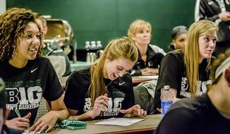 Madison Williams, left, Annalise Pickrel, center, and Becca Mills ofMichigan Statue University begin to complete their bracket sheets as the MSU Women's Basketball team's NCAA bracket is announced Monday March 17, 2014 at the Breslin Center in East Lansing.  (AP Photo/The State Journal, Kevin W. Fowler)  NO SALES