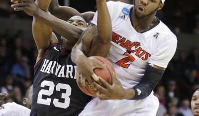 Cincinnati's Titus Rubles, right, gets tangled-up with Harvard's Wesley Saunders (23) and Kyle Casey in the second half of a second-round game of the NCAA college basketball tournament in Spokane, Wash., Thursday, March 20, 2014. (AP Photo/Elaine Thompson)