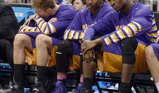 Albany's David Wiegmann, left, Reece Williams and Ede Egharevba, right, sit on the bench during the second half in a second-round game in the NCAA college basketball tournament against Florida, Thursday, March 20, 2014, in Orlando, Fla. Florida won 67-55. (AP Photo/Phelan M. Ebenhack)