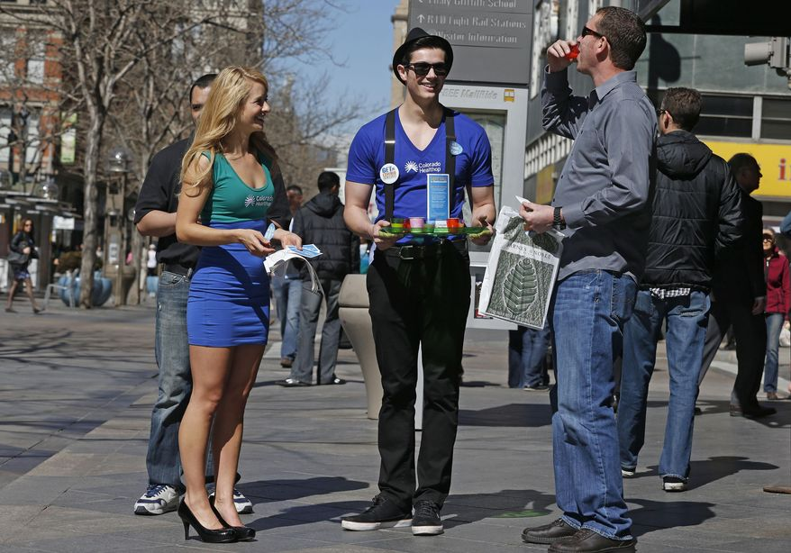 Meghan McMahon, left, and fellow model Alex Terranova hand out stickers and juice shots on an outdoor pedestrian mall, encouraging the public to get health coverage under the Affordable Care Act, during a promotional campaign launched by Colorado HealthOP, a independent non-profit health care co-op, in Denver, Thursday March 20, 2014. More than 250,000 Coloradans have become covered through the state-run insurance exchange since enrollment began October 1, 2013, and those who still do not have health insurance have two more weeks to get coverage or pay a fine. (AP Photo/Brennan Linsley)
