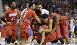 Dayton teammates embrace Vee Sanford, center, after defeating Ohio State in a second-round game in the NCAA college basketball tournament against Ohio State in Buffalo, N.Y., Thursday, March 20, 2014.  Sanford scored on a layup with 3.8 seconds left to lift 11th-seeded Dayton to a 60-59 win. (AP Photo/Frank Franklin II)
