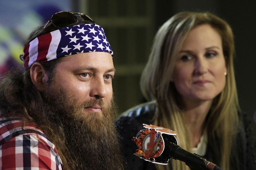 """Duck Dynasty stars Willie and Korie Robertson at Texas Motor Speedway as they debuted their new Big Hoss TV, a 218 x 94 foot screen over the east grandstands of the racetrack, Wednesday, March 19, 2014. The first show to be seen on the screen by the public is Wednesday's episode of """"Duck Dynasty"""", sponsors of the upcoming April NASCAR race, the Duck Commander 500.  (AP Photo/The Fort Worth Star-Telegram, Paul Moseley)"""