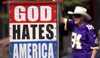This file photo shows Fred Phelps Sr. displays one of his many infamous protest signs. Phelps, the fiery founder of the Westboro Baptist Church, a small Kansas church,  who drew international condemnation for outrageous and hate-filled protests that blamed almost everything, including the deaths of AIDS victims and U.S. soldiers, on America's tolerance for gay people, has died the family said Thursday, March 20, 2014. He was 84.  (AP Photo/The Topeka Capital Journal)