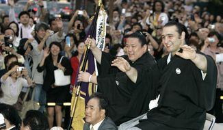 FILE - In this May 25, 2008 file photo, Bulgarian-born sumo wrestler Kotooshu, right, waves from a convertible during a parade outside the Ryogoku Kokugikan sumo arena in Tokyo. Kotooshu, the first European wrestler to win an Emperor's Cup, said Thursday, March 20, 2014, he has decided to retire. The 31-year-old Kotooshu, whose real name is Karoyan Ando, was promoted to sumo's second-highest rank of ozeki in 2005 and won the Emperor's Cup in 2008 for his only championship at the elite level. (AP Photo/Shizuo Kambayashi, File)