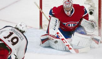 Columbus Blue Jackets' Ryan Johansen, left, scores against Montreal Canadiens goaltender Carey Price during the third period of an NHL hockey game in Montreal, Thursday, March 20, 2014. (AP Photo/The Canadian Press, Graham Hughes)