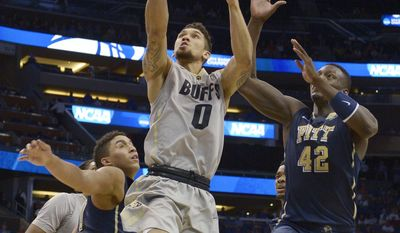 Pittsburgh guard James Robinson, left, and forward Talib Zanna, right, defend as Colorado guard Askia Booker (0) shoots during the second half in a second-round game in the NCAA college basketball tournament Thursday, March 20, 2014, in Orlando, Fla. (AP Photo/Phelan M. Ebenhack)