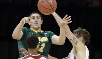 North Dakota State's Marshall Bjorklund passes between Oklahoma players in the first half during a second-round game of the NCAA men's college basketball tournament, in Spokane, Wash., Thursday, March 20, 2014. (AP Photo/Elaine Thompson)