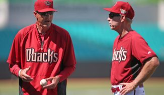 The Arizona Diamondbacks' manager Kirk Gibson, left, talks with Diamondbacks' bench coach Alan Trammell at the Sydney Cricket Ground in Sydney, Thursday, March 20, 2014. The Diamondbacks and Los Angeles Dodgers open the MLB regular season with games on Saturday and Sunday. (AP Photo/Rick Rycroft)