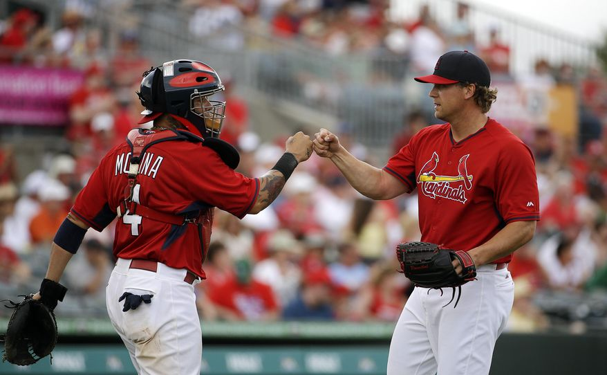 St. Louis Cardinals relief pitcher Trevor Rosenthal, right, fist-bumps catcher Yadier Molina after closing out the ninth inning of an exhibition spring training baseball game against the Washington Nationals, Friday, March 21, 2014, in Jupiter, Fla. (AP Photo/David Goldman)