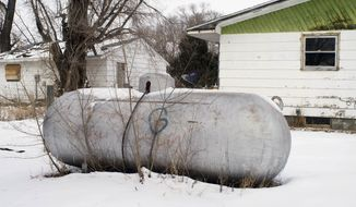 FILE - This Feb. 6, 2014 file photo shows a propane tank outside a home on the Standing Rock Reservation in Fort Yates, N.D. Donations from an American Indian tribe in Minnestoa totalling nearly $1.4 million have helped tribes in the Great Plains deal with a winter propane crisis. The Shakopee Mdewakanton Sioux Community provided grants to five tribes in the Dakotas and Nebraska. (AP Photo/Kevin Cederstrom, File)