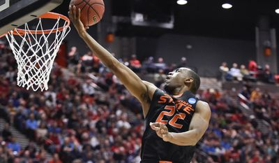 Oklahoma State guard Markel Brown sails to the basket for a score against Gonzaga during the second half in a second-round game in the NCAA college basketball tournament Friday, March 21, 2014, in San Diego. (AP Photo/Denis Poroy)