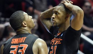 Oklahoma State's Marcus Smart, left, looks to the scoreboard as teammate Kamari Murphy shows his frustration during the second half of their 85-77 loss to Gonzaga in a second-round game in the NCAA college basketball tournament Friday, March 21, 2014, in San Diego. (AP Photo/Denis Poroy)