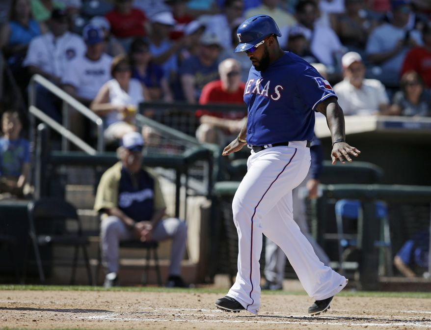 Texas Rangers' Prince Fielder gives the signals safe after scoring on a sacrifice fly during the fifth inning of a spring exhibition baseball game against the Milwaukee Brewers Friday, March 21, 2014, in Surprise, Ariz. (AP Photo/Darron Cummings)