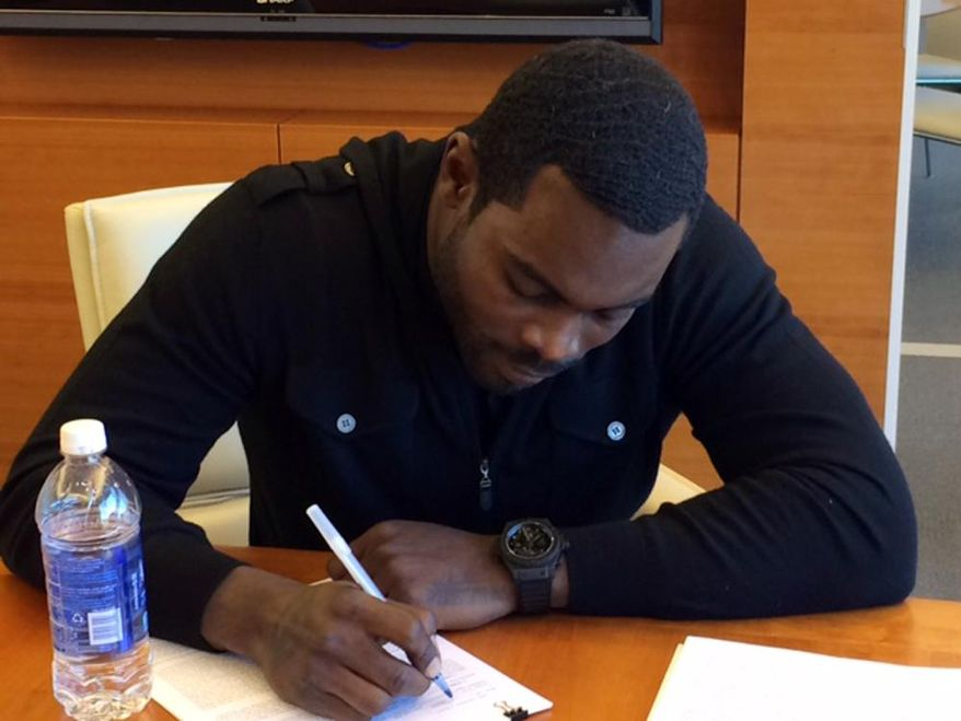 In this image released by the New York Jets, NFL football free-agent quarterback Michael Vick signs with the New York Jets Friday, March 21, 2014, in Florham Park, N.J. The Jets signed the former Philadelphia Eagles quarterback to a one-year deal on Friday, and released Mark Sanchez, the one-time face of the franchise. (AP Photo/New York Jets, @nyjets)