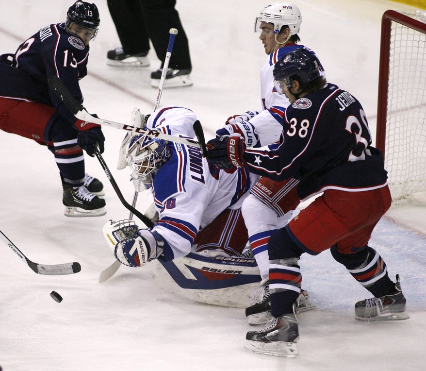 New York Rangers goalie Henrik Lundqvist (30) dives for the puck during the third period of an NHL hockey game against the Columbus Blue Jackets, Friday, March 21, 2014, in Columbus, Ohio. The Rangers won 3-1.  (AP Photo/Mike Munden)