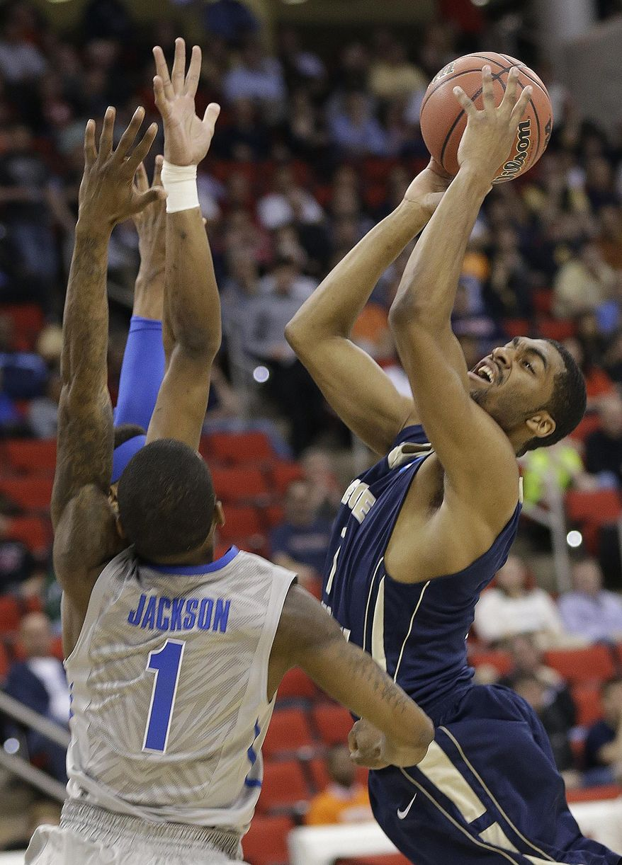George Washington guard Maurice Creek (1) heads to the hoop against Memphis guard Joe Jackson (1) during the first half of an NCAA college basketball second-round tournament game, Friday, March 21, 2014, in Raleigh. (AP Photo/Gerry Broome)