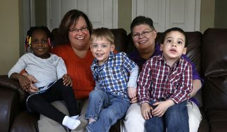 FILE - In this March 5, 2013, file photo, April DeBoer, second from left, sits with her adopted daughter Ryanne, 3, left, and Jayne Rowse, fourth from left, and her adopted sons Jacob, 3, middle, and Nolan, 4, right, at their home in Hazel Park, Mich. A federal judge has struck down Michigan's ban on gay marriage, Friday, March 21, 2014, the latest in a series of decisions overturning similar laws across the U.S. The two nurses who've been partners for eight years claimed the ban violated their rights under the U.S. Constitution. (AP Photo/Paul Sancya, File)