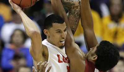 New Mexico's Kendall Williams, left, looks to pass under pressure from Stanford's Josh Huestis (24) during the first half of a second-round game in the NCAA college basketball tournament, Friday, March 21, 2014, in St. Louis. (AP Photo/Charlie Riedel)