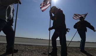 In this March 20, 2014 photo, United States Marine Corps veterans Mokie Surratt, of Peoria, center, and Walt Sandall of Green Valley, place flags on Main Street in Hopedale, Ill. in honor of 32-year-old Capt. Reid Nannen, who died March 1 when his jet crashed during a training exercise in Nevada. More than 100 volunteers turned out in Hopedale, a town of about 850, to plant 2,380 flags along 12 miles of highway in honor of the 32-year-old Marine. Nannen's funeral is Saturday, and townspeople wanted to do something special for their native son. (AP photo/The Pantagraph, Steve Smedley)