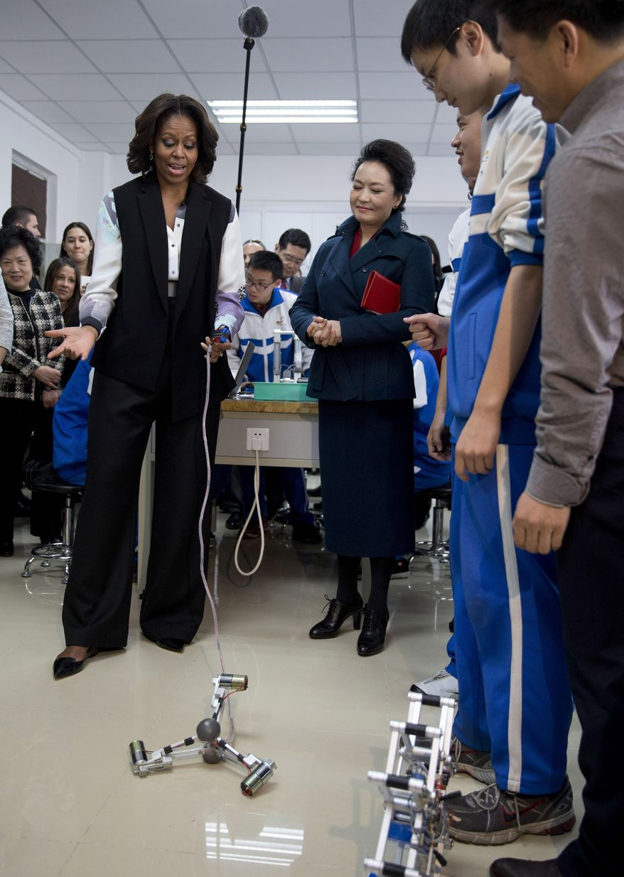 U.S. first lady Michelle Obama, left, tries out a remote control mechanical robot next to Peng Liyuan, wife of Chinese President Xi Jinping as they visit the Beijing Normal School, a school that prepares students to attend university abroad in Beijing, China Friday, March 21, 2014. (AP Photo/Andy Wong, Pool)