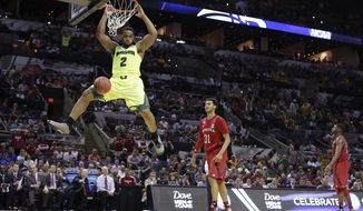 Baylor's Rico Gathers (2) scores as Nebraska's Shavon Shields (31) looks on during the first half of a second-round game in the NCAA college basketball tournament Friday, March 21, 2014, in San Antonio. (AP Photo/Eric Gay)