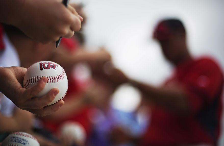A fan holds out a baseball while waiting for an autograph from St. Louis Cardinals' Kolten Wong, right, following an exhibition spring training baseball game against the Washington Nationals, Friday, March 21, 2014, in Jupiter, Fla. (AP Photo/David Goldman)