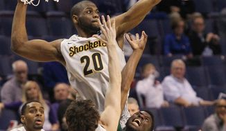 Wichita State center Kadeem Coleby, TOP, blocks a shot by Cal Poly forward David Nwaba during the first half of a second-round game in the NCAA college basketball tournament Friday, March 21, 2014, in St. Louis. (AP Photo/St. Louis Post-Dispatch, Chris Lee)  EDWARDSVILLE INTELLIGENCER OUT; THE ALTON TELEGRAPH OUT