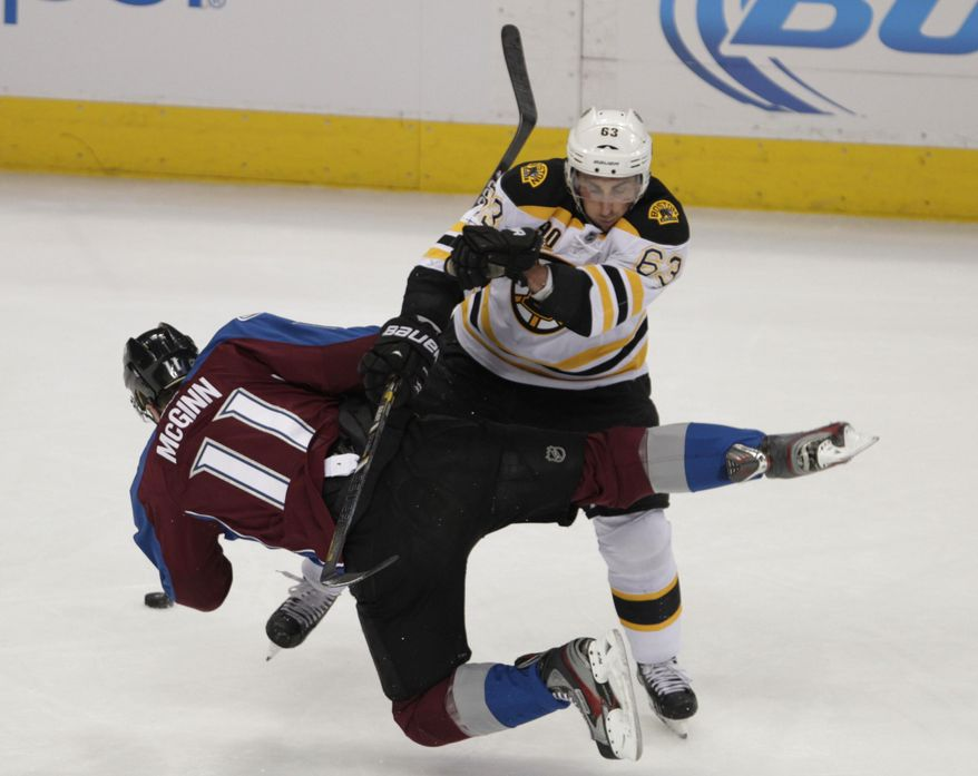 Colorado Avalanche left wing Jamie McGinn (11) collides with Boston Bruins left wing Brad Marchand (63) the first period of an NHL hockey game in Denver on Friday, March 21, 2014.(AP Photo/Joe Mahoney)
