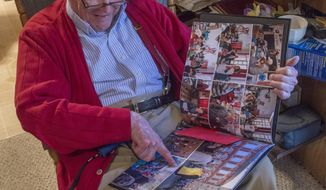 Everett Andrews looks over a photo album of recent pictures made in Bastogne, Belgium.  And this December, some 70 years after hundreds of colored parachutes kept the 101st Airborne Division alive in the cut-off city of Bastogne, Belgium, Andrews plans to return to the French countryside with a gift of his own. (AP Photo/The Fayetteville Observer, Johnny Horne)