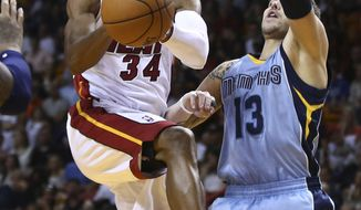 Memphis Grizzlies' Mike Miller (13) defends MIami Heat's Ray Allen (34) during the first half of an NBA basketball game in Miami, Friday, March 21, 2014. (AP Photo/J Pat Carter)