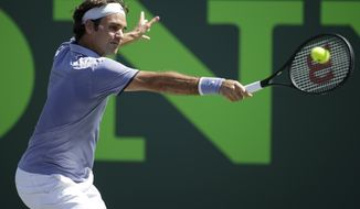 Roger Federer, of Switzerland, returns the ball to Ivo Karlovic, of Croatia, at the Sony Open tennis tournament, Friday, March 21, 2014, in Key Biscayne, Fla. Federer defeated Karlovic 6-4, 7-6 (7-4). (AP Photo/Lynne Sladky)