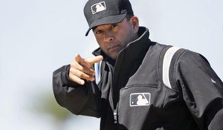 FILE - In this March 13, 2014 file photo, umpire Angel Campos signals for a replay during a spring exhibition baseball game between the Detroit Tigers and the Miami Marlins in Lakeland, Fla. Some teams have hired a person who will watch the clubhouse TV and decide whether it's worth challenging an umpire's call. Other clubs don't want to say exactly how they'll do it. Either way, the job of replay coordinator has become a big one.  (AP Photo/Carlos Osorio, File)
