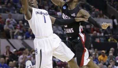 Creighton's Austin Chatman (1) scores as Louisiana-Lafayette's Bryant Mbamalu (0) defends him during the second half of a second-round game in the NCAA college basketball tournament Friday, March 21, 2014, in San Antonio. Creighton won 76-66.(AP Photo/Eric Gay)