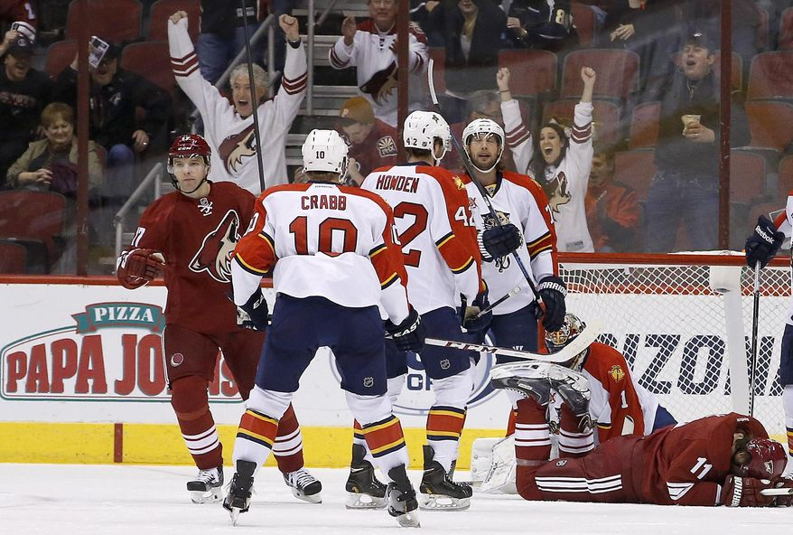 Phoenix Coyotes' Radim Vrbata, left, of the Czech Republic, pumps his fist after scoring against Florida Panthers' Roberto Luongo (1) as Panthers' Joey Crabb (10), Quinton Howden (42) and Tom Gilbert stand near the goal as Coyotes' Martin Hanzal (11), of the Czech Republic, stays on the ice after getting a puck to the foot, during the first period of an NHL hockey game, Thursday, March 20, 2014, in Glendale, Ariz. (AP Photo/Ross D. Franklin)